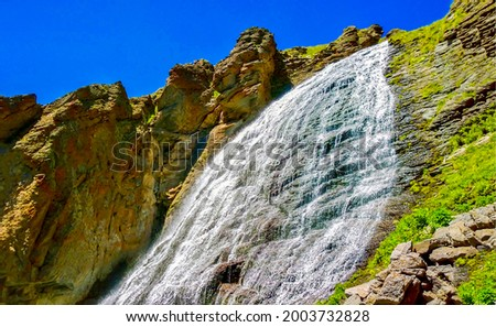 Mountain waterfall falls from a cliff. Mountain waterfall. Waterfall in mountains