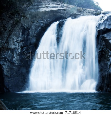 Mountain waterfall, like a piece of white cloth floating down.