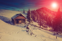 Mountain winter landscape.View of the  old farm. Fantastic evening glowing by sunlight.Retro filter.