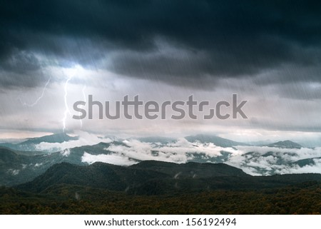 mountain with sky and lighting under rain