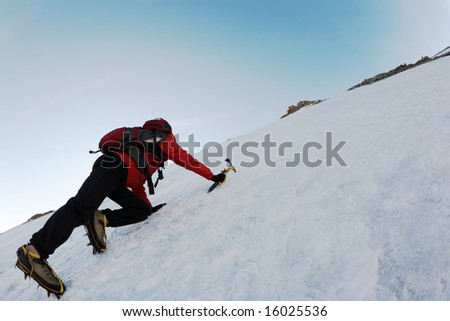 Mountaineer climbing a steep route on a icy slope, italian Alps, Europe.