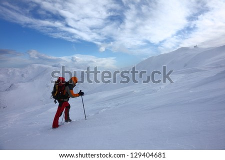 Mountaineer climbing the mountain under strong winds, Romania