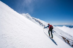 Mountaineer climbs snowfield on a sunny day high on a mountain.