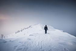 Mountaineer man walking on snowy mountain ridge with blizzard in gloomy weather at Senja island, Norway