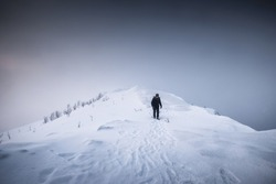 Mountaineer man walking on snowy mountain ridge with blizzard in gloomy weather at Senja island, Norway