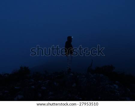 Mountaineer on a peak in fog