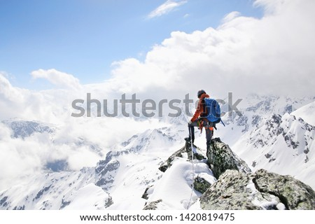Photo of  mountaineer on the top of a mountain in the background of the landscape of snowy mountains