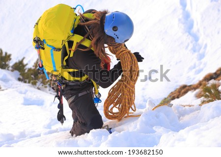 Mountaineer packs the climbing rope in winter