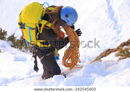 Mountaineer packs the rope after climbing in winter