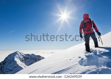 Mountaineer reaches the top of a snowy mountain in a sunny winter day. Western Alps, Biella, Italy. #126269039