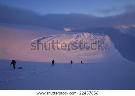 Mountaineering team ascending the upper Kahiltna Glacier to 11,200 camp, at around midnight, on Denali, Denali National Park, Alaska.