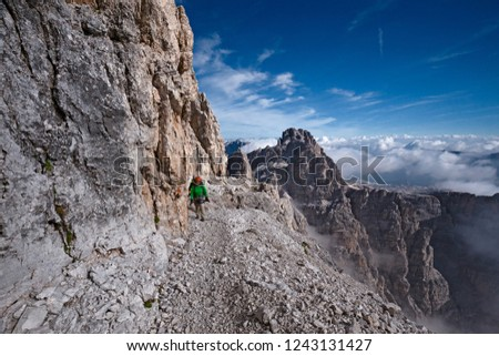 """Mountaineers equipped face the """"Bocchette Alte"""" ferrata in the Brenta group on the Dolomites, in Italy #1243131427"""