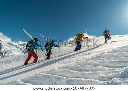 Mountaineers walking up along a snowy ridge with the skis in the backpack. Skier on the climbing track for freeride-descent. Backcountry skiers. ski free rider climbs the slope into deep snow powder.