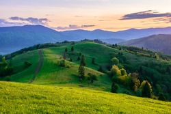 mountainous countryside in springtime at dusk. path uphill in to the distance. trees on the rolling hills. ridge in the distance. clouds on the sky. beautiful rural landscape of carpathians
