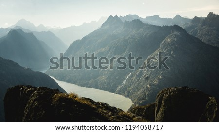 Mountainous panorma landscape view with big mountains. Mountain Pass in Switzerland. Autumn mood at sunset. Grimsel Pass links the Hasli Valley in the Bernese Oberland with Goms in Valais.  #1194058717