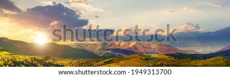 mountainous rural panorama landscape in springtime at sunset. beautiful scenery beneath a sky with clouds in evening light. grass covered hill rolling in to the distant ridge Foto stock ©