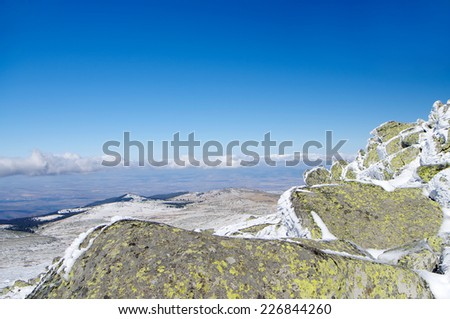 Mountainous winter landscape with rocks and blue sky