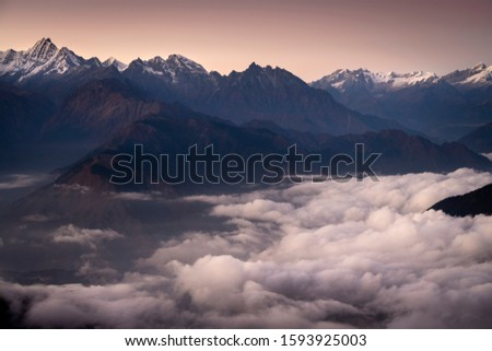 Mountains above clouds. Langtang National Park, Nepal. Landscape with mountain valley covered with low clouds, bright sky  at sunset.