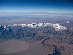 Mountains aerial view. Mountain peaks is covered snow. On foothills of mountains is hot and desert. Over horizon a clear blue sky.