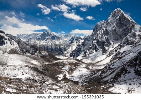 Mountains Ama Dablam, Cholatse, Tabuche Peak at the blue sky with clouds on a sunny day