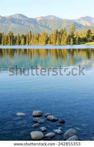 Mountains and Evergreen Forest Reflected in Blue Lac Beauvert, Jasper National Park, Alberta, Canada