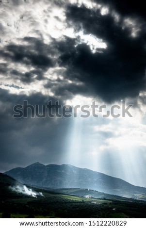 Mountains and field under cloudy sky with sunbeams falling on it #1512220829