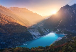 Mountains and lake with blue water at sunset in Nepal. Majestic landscape with high mountains, lake, lightened hills, rocks, yellow sunlight and blue sky. Bright sunny evening. Travel. Nature