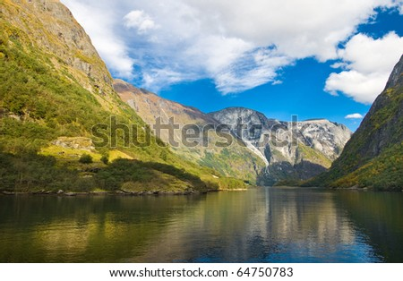 Mountains and norwegian fjord in autumn. Clouds and blue sky