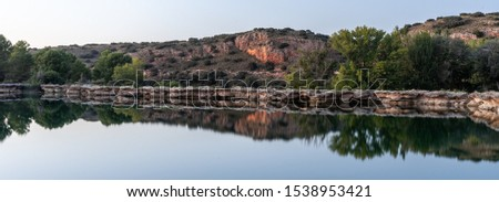 mountains and rocks reflected in the water as if it were a mirror #1538953421