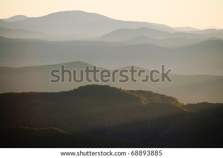 mountains at sunrise in fog - stock photo