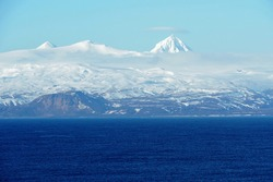 Mountains covered with snow in Aleutian Islands as a part of island chain in Alaska observed form container vessel sailing over Pacific ocean during sunny winter weather and calm sea.