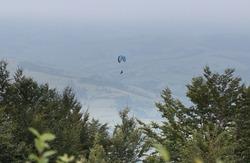 Mountains, fog, Paraglider. Parachuter. Paragliding in mountains. Paragliding sport.Parachute jumper.Parachute. Extreme sports activity