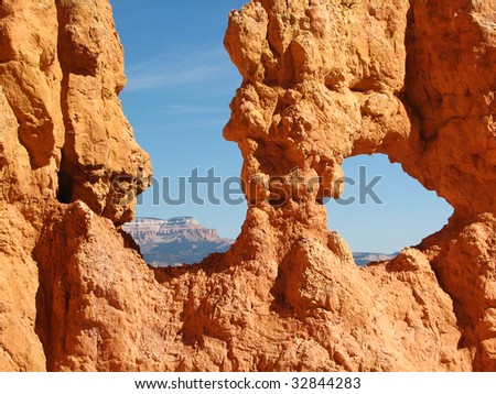 Mountains framed by the holes in the multicoloured Hoodoos at Bryce Canyon