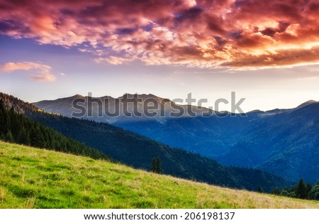 Mountains glow by sunlight. Morning overcast sky. Dramatic scenery. Carpathian, Ukraine, Europe. Beauty world.