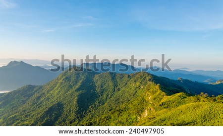 Mountains green grass and blue sky landscape #240497905