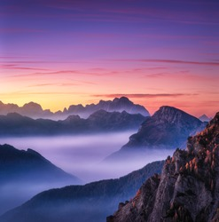 Mountains in fog at beautiful sunset in autumn in Dolomites, Italy. Landscape with alpine mountain valley, low clouds, trees on hills, purple sky with clouds at dusk. Aerial view. Passo Giau. Nature