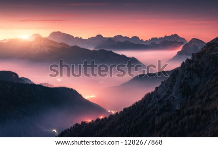Mountains in fog at beautiful sunset in autumn in Dolomites, Italy. Landscape with alpine mountain valley, low clouds, forest, purple sky city illumination at twilight. Aerial view. Passo Giau