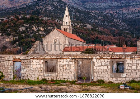 Mountains landscape of a small croatian town with abandoned building on foreground, catholic church and bell-cote tower in the middle, mountains on background