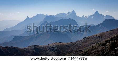 Mountains of Tajikistan in the distance turned blue from hazy afternoon and long distance #714449896