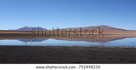 Mountains reflected in a desert lake against a bright blue sky at Salar de Uyuni, Bolivia #792498250