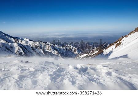Mountains under the snow in winter. Panorama of snow mountain range landscape with blue sky. #358271426