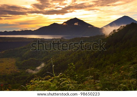 Mountains with lake (Batur) in caldera and wet grass on the foreground at sunrise