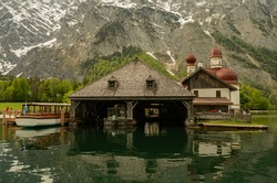 Mountains with snow, on top of a mountain with a beautiful church with green water and a boat parking, walking