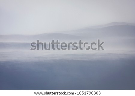 Mountainside in strong wind, snowstorm. Its whiteout in a blizzard. #1051790303