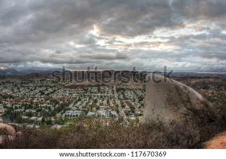 Mountaintop view of a dorsal fin shaped boulder, ominous storm clouds, and suburban San Diego County in the evening.
