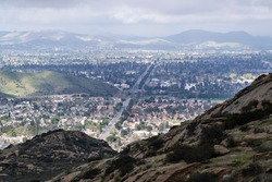 Mountaintop view of clearing skies and suburban streets and homes along Los Angeles Ave in Simi Valley, California.