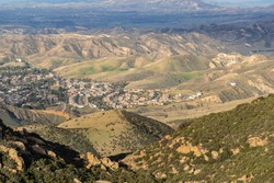 Mountaintop view of suburban streets and homes spreading towards open hillsides in Simi Valley, California.