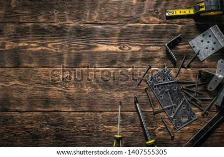 Mounting plates and woodwork tools on a wooden workbench. Construction or carpentry flat lay background with copy space. Under construction concept. #1407555305