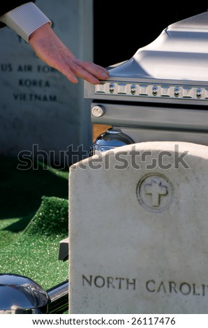 Mourner touching casket at Arlington National Cemetery