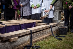 Mourners staying by the opened grave, burying a coffin at a cemetery during a funeral ceremony